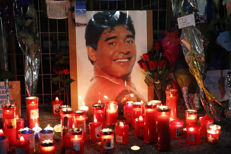 Candles and flowers are seen outside the San Paolo stadium commemorating soccer legend Diego Maradona, in Naples, Thursday, Nov. 26, 2020. Maradona died on Wednesday at the age of 60 of a heart attack in a house outside Buenos Aires where he recovered from a brain operation. (AP Photo/Alessandra Tarantino)