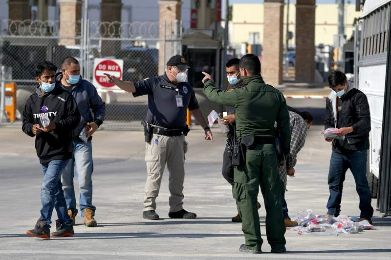 FILE - U.S. Customs and Border Protection officers, center, instruct migrants to walk toward the McAllen-Hidalgo International Bridge while deporting them to Mexico, Saturday, March 20, 2021, in Hidalgo, Texas. The fate of thousands of migrant families who have recently arrived at the Mexico border is being decided by a mysterious new system under President Joe Biden. U.S. authorities are releasing migrants with acute vulnerabilities and allowing them to pursue asylum. But it's not clear why some are considered vulnerable and not others. (AP Photo/Julio Cortez)