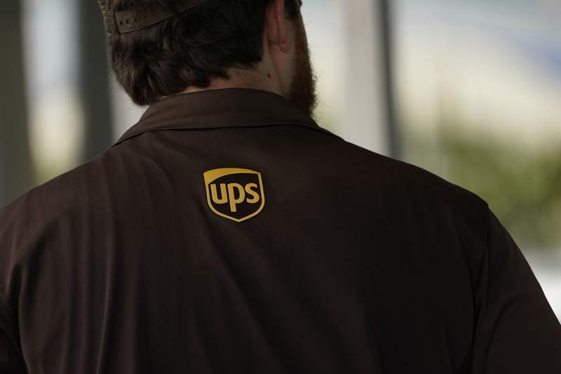A UPS logo is on the shirt of a driver as he enters a United Parcel Service store with packages in Jackson, Miss., Monday, July 26, 2021. The Atlanta-based company said Thursday, Sept. 9,  that it plans to hire more than 100,000 people for the busy holiday shipping season, many of whom will get job offers within 30-minutes of applying. UPS needs to snap up workers as fast as it can because of the tight job market.  (AP Photo/Rogelio V. Solis)
