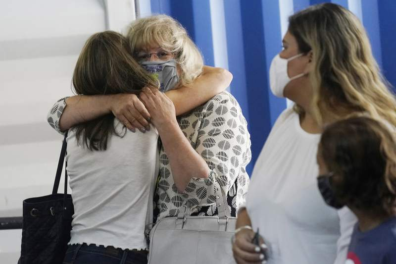 Bonnie Schawtzeaum, center, hugs Sharon Schechter, left, during an event where survivors of the Champlain South Towers collapse received relocation funds, Wednesday, July 28, 2021, in Doral, Fla. Schechter was in her apartment on the 11th floor when the building collapsed on June 24. Global Empowerment Mission and other charities have provided funds to pay the first and last months rent and security deposit at new apartments for Schechter and about 30 other individuals and families. (AP Photo/Marta Lavandier)