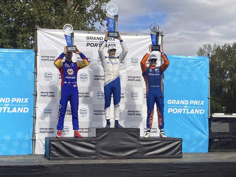 Alex Palou, center, celebrates his third IndyCar win of the season on Sunday, Sept. 12, 2021 at Portland International Raceway in Portland, Ore. Palous win moved him back atop the IndyCar championship standings with two races remaining. Alexander Rossi finished second and Scott Dixon, teammates with Palou at Chip Ganassi Racing, finished third. (AP Photo/Jenna Fryer)