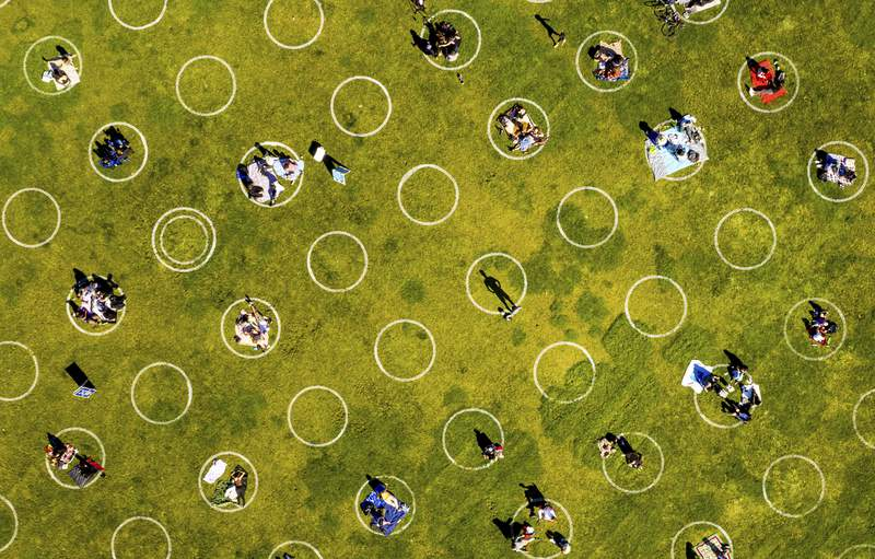 FILE - In this Thursday, May 21, 2020 file photo, circles designed to help prevent the spread of the coronavirus by encouraging social distancing are placed in San Francisco's Dolores Park. Recovering from even mild coronavirus infections can take at least two to three weeks, according to U.S. research published online Friday, July 24, 2020. (AP Photo/Noah Berger)