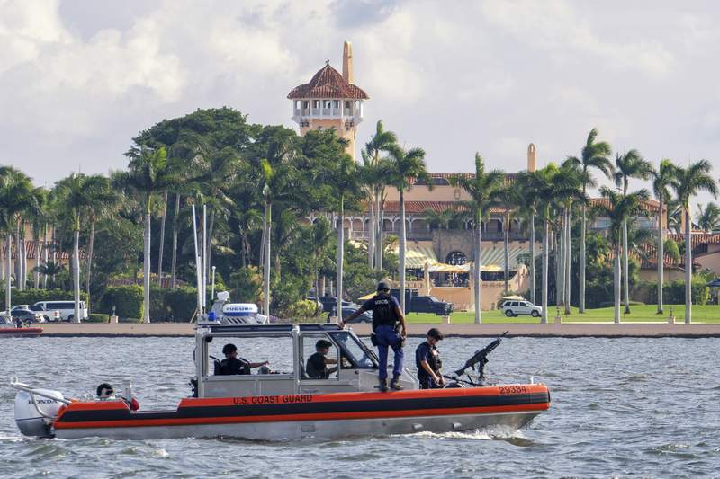 FILE - In this Nov. 22, 2018 file photo, a U.S. Coast Guard patrol boat passes President Donald Trump's Mar-a-Lago estate in Palm Beach, Fla. Trump's expected move to his Mar-a-Lago club after he leaves office next month is being challenged by a lawyer who says a 1990s agreement allowing Trump to convert the property into a business prohibits anyone from living there, including him.  (AP Photo/J. David Ake, File)