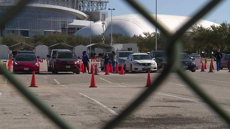 Vehicles wait at a drive-thru vaccine clinic held at NRG Park in Houston on Jan. 15, 2021.