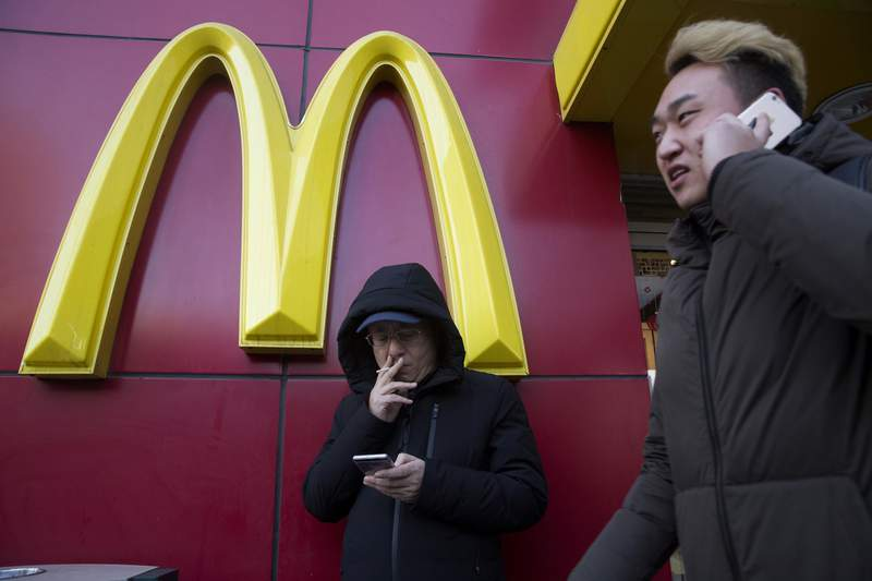 FILE - In this Jan. 10, 2017, file photo, a man smokes outside a McDonald's restaurant in Beijing, China. McDonalds is selling a sandwich made of Spam topped with crushed Oreo cookies Monday, Dec. 21, 2020 in China in an attention-grabbing move that has raised eyebrows. (AP Photo/Ng Han Guan, File)