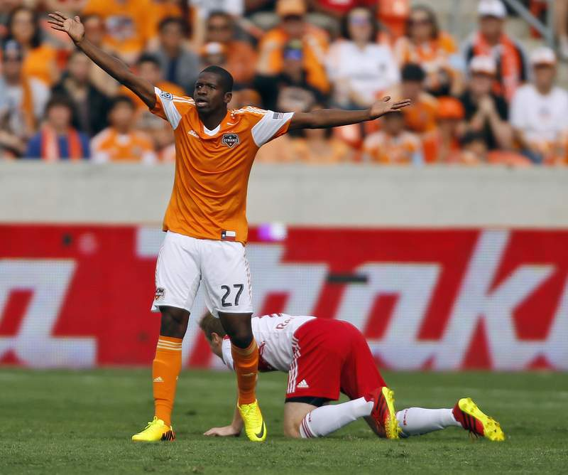 Houston Dynamo's Oscar Boniek Garcia, left, protests a penalty as New York Red Bulls' Dax McCarty gets up off the pitch during the first half of an MLS Eastern Conference semifinal playoff match, Sunday, Nov. 3, 2013, in Houston. (AP Photo/Eric Christian Smith)