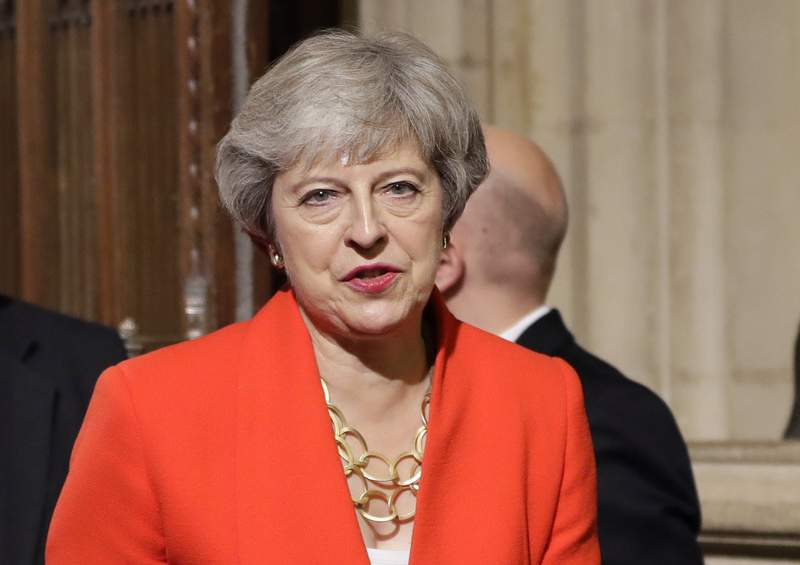 FILE - In this Monday, Oct. 14, 2019 file photo, Britain's former Prime Minister Theresa May walks through the Commons Members Lobby in Parliament, London. British Prime Minister Boris Johnson welcomed the start of a new U.K.-U.S. chapter on Wednesday Jan. 20, 2021, under incoming U.S. President Joe Biden, even as his predecessor Theresa May accused Johnson of abandoning the U.K.s moral leadership in the world during the tumultuous Trump era. (AP Photo/Kirsty Wigglesworth, pool, file)