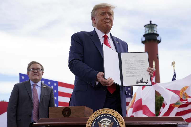 FILE - In this Sept. 8, 2020, file photo President Donald Trump holds a signed memorandum to expand the offshore drilling moratorium to Florida's Atlantic coast, Georgia and South Carolina after speaking at the Jupiter Inlet Lighthouse and Museum in Jupiter, Fla. At left is Environmental Protection Agency Administrator Andrew Wheeler. With one stroke, Trumps abrupt reversal on offshore drilling this week has loosened a political vise that was tightening around three Republicans senators running for reelection in coastal states where drilling is widely opposed. (AP Photo/Evan Vucci, File)