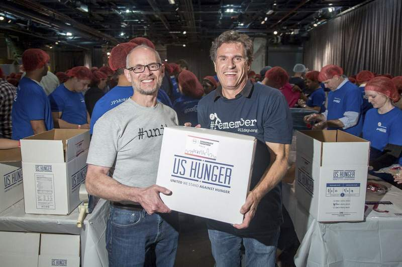 In this Sept. 11, 2017 photo, 9/11 Day co-founders Jay Winuk, left, and David Paine pack meals for food bank distribution on Sept. 11, 2017 at the Intrepid Sea, Air and Space Museum in New York. To mark the 20th anniversary of the terrorist attacks that killed thousands, including Winuks younger brother, Glenn, the 9/11 Day co-founders are expanding their efforts with a CNN special Shine a Light airing on Saturday, Sept. 11, 2021.   (9/11 Day via AP)