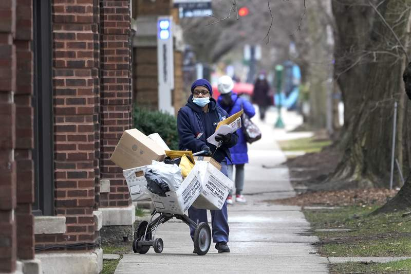 """FILE - A U.S. postal worker delivers packages, boxes and letters Tuesday, Dec. 22, 2020, along her route in the Hyde Park neighborhood of Chicago, just three days before Christmas.  Some Christmas gift-givers discovered their presents didn't arrive in time for the holiday despite ordering weeks ahead. The U.S. Postal Service says it faces """"unprecedented volume increases and limited employee availability due to the impacts of COVID-19.  (AP Photo/Charles Rex Arbogast)"""