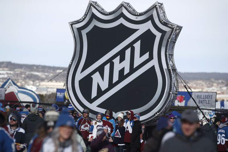 FILE - In this Saturday, Feb. 15, 2020, file photo, fans pose below the NHL league logo at a display outside Falcon Stadium before an NHL Stadium Series outdoor hockey game between the Los Angeles Kings and Colorado Avalanche, at Air Force Academy, Colo. The NHL Players Associations executive board is voting on a 24-team playoff proposal as the return-to-play format, a person with knowledge of the situation told The Associated Press, late Thursday, May 21, 2020. (AP Photo/David Zalubowski, File)