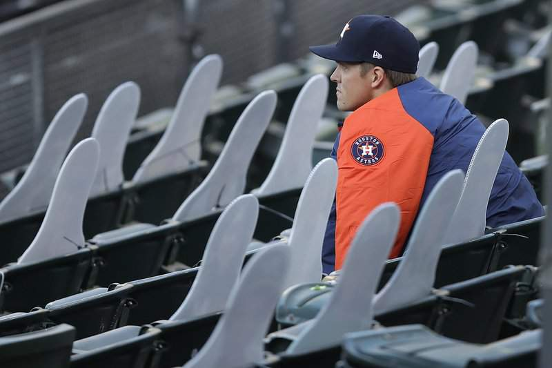 Houston Astros pitcher Zack Greinke socially distances himself beside cardboard cutout fans in the stands of the Oakland Coliseum in the fourth inning of a baseball game against the Oakland Athletics on Friday, Aug. 7, 2020, in Oakland, Calif.