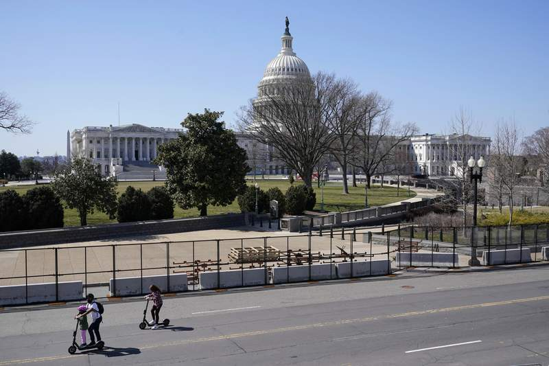 People ride scooters past an inner perimeter of security fencing on Capitol Hill in Washington, Sunday, March 21, 2021, after portions of an outer perimeter of fencing were removed overnight to allow public access. (AP Photo/Patrick Semansky)