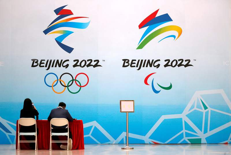 Staff members sit near a board with signs of the 2022 Olympic Winter Games, at the National Aquatics Center in Beijing, China, on April 1, 2021.