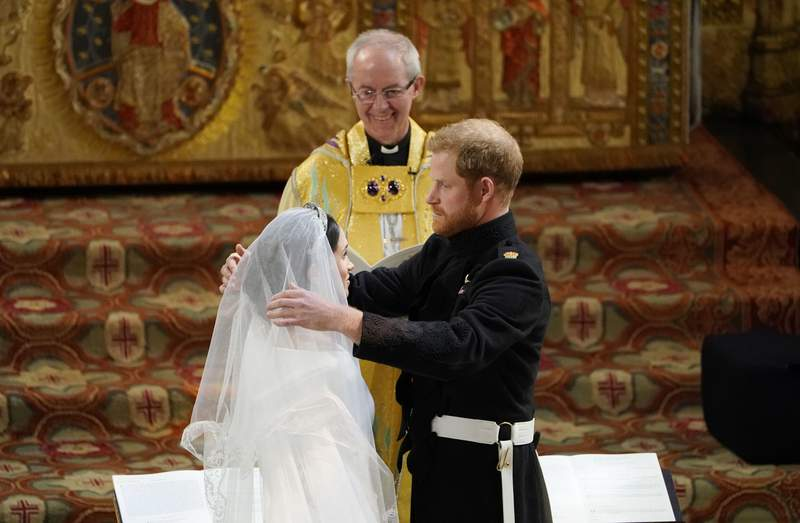 FILE - In this Saturday, May 19, 2018 file photo, Britain's Prince Harry pulls back the veil of Meghan Markle watched by Archbishop of Canterbury Justin Welby during their wedding at St. George's Chapel in Windsor Castle in Windsor, near London, England. The archbishop of Canterbury has confirmed that he married Prince Harry and Meghan Markle at Windsor Castle in May 2018, despite the couples claim they had another, private, ceremony three days earlier. During an interview with Oprah Winfrey earlier this month, Meghan said that three days before our wedding we got married. (Owen Humphreys/pool photo via AP, File)