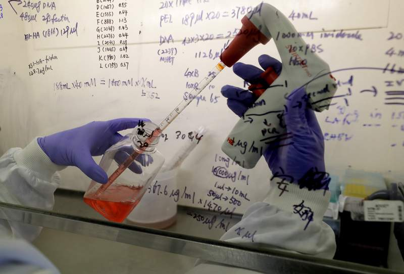 FILE - In this July 30, 2020 file photo, Kai Hu, a research associate transfers medium to cells, in the laboratory at Imperial College in London. Imperial College is working on the development of a COVID-19 vaccine. South Africa and India on Friday Oct. 2, 2020, asked the World Trade Organization to waive some provisions in the international agreements that regulate intellectual property rights, to speed up efforts to prevent, treat and contain the COVID-19 pandemic and make sure developing countries are not left behind. (AP Photo/Kirsty Wigglesworth, File)