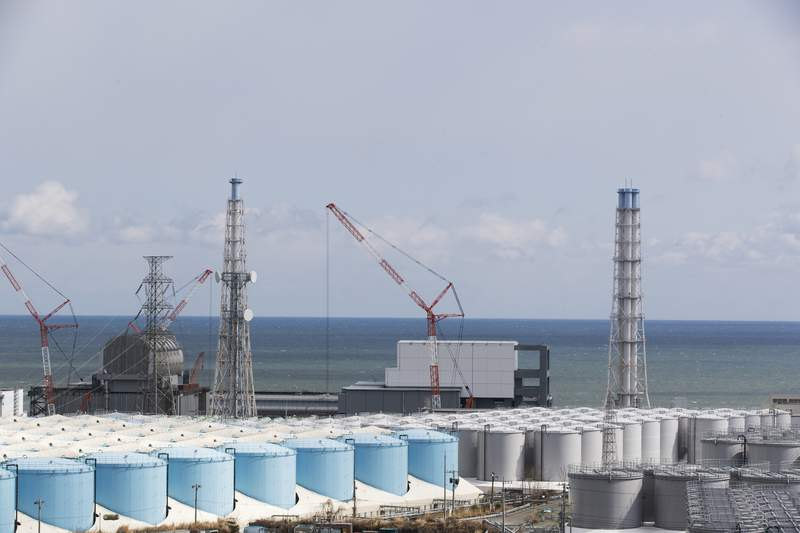 FILE - In this Feb. 27, 2021, file photo, the Pacific Ocean looks over nuclear reactor units of No. 3, left, and 4 at the Fukushima Daiichi nuclear power plant in Okuma town, Fukushima prefecture, northeastern Japan. Japans government adopted an interim plan Tuesday, Aug. 24, 2021 that it hopes will win support from fishermen and other concerned groups for a planned release into the sea of treated but still radioactive water from the wrecked Fukushima nuclear plant. The government decided in April to start discharging the water into the Pacific Ocean in the spring of 2023 after building a facility and compiling release plans under safety requirements set by regulators (AP Photo/Hiro Komae, File)