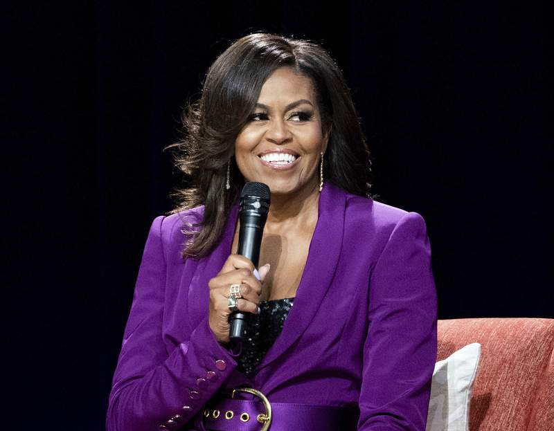 """FILE - This May 11, 2019 file photo shows former first lady Michelle Obama during """"Becoming: An Intimate Conversation with Michelle Obama,"""" in Atlanta. The Obamas Higher Ground and Spotify announced Thursday that the former first lady will host The Michelle Obama Podcast on the streaming service. The podcast will debut exclusively on Spotify on July 29.  (Photo by Paul R. Giunta/Invision/AP, File)"""