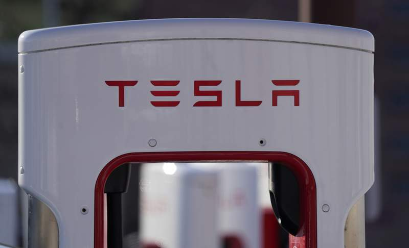 FILE - The company logo is shown at the top of a supercharger for Tesla automobiles near shops Feb. 25, 2021 in Boulder, Colo. Tesla's quarterly profit has surpassed $1 billion for the first time thanks to the electric car pioneer's ability to navigate through a pandemic-driven computer chip shortage that has caused major headaches for other automakers. The financial milestone announced Monday, July 26, 2021 extended a two-year run of prosperity that has erased questions about Teslas long-term viability raised during its early years of losses and production problems. (AP Photo/David Zalubowski, file)