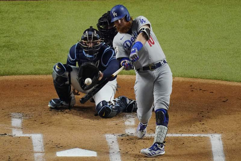FILE - In this Oct. 24, 2020, file photo, Los Angeles Dodgers' Justin Turner hits a home run against the Tampa Bay Rays during the first inning in Game 4 of the baseball World Series in Arlington, Texas. Turner is returning to the Dodgers, announcing via Twitter that hes ready to run it back with the World Series champions. (AP Photo/Sue Ogrocki, File)