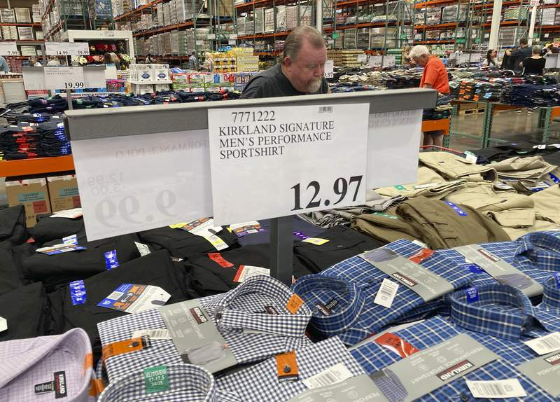 A sign displays the price for shirts as a shopper peruses the offerings at a Costco warehouse in this photograph taken Thursday, June 17, 2021, in Lone Tree, Colo.  Growth in U.S. consumer spending slowed in July to a modest increase of 0.3% while inflation over the past 12 months rose to the fastest pace in three decades.  (AP Photo/David Zalubowski)