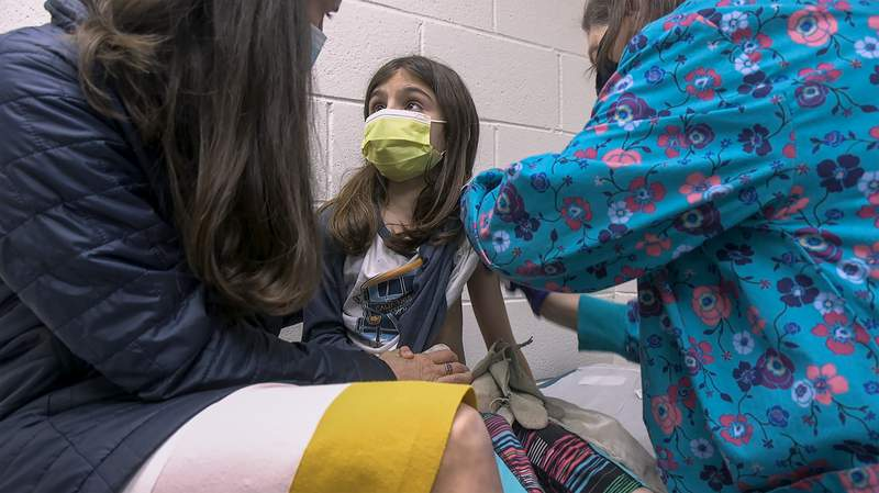 In this Wednesday, March 24, 2021 image from video provided by Duke Health, Alejandra Gerardo, 9, looks up to her mom, Dr. Susanna Naggie, as she gets the first of two Pfizer COVID-19 vaccinations during a clinical trial for children at Duke Health in Durham, N.C. In the U.S. and abroad, researchers are beginning to test younger and younger kids, to make sure the shots are safe and work for each age. (Shawn Rocco/Duke Health via AP)