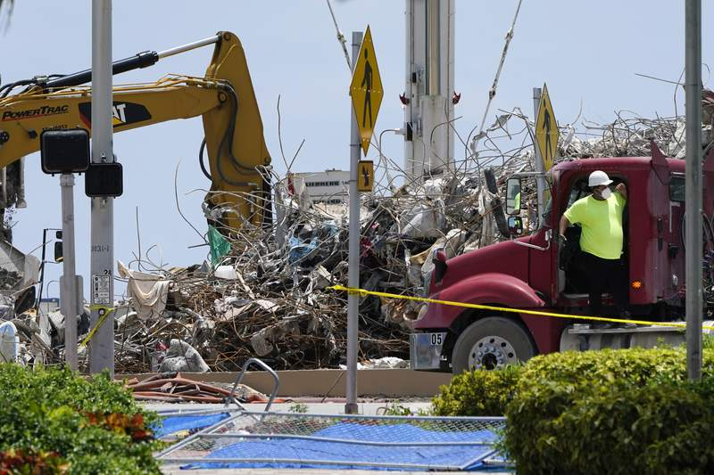 A worker waits to load his truck with debris from the rubble of the Champlain Towers South building, as removal and recovery work continues at the site of the partially collapsed condo building, Wednesday, July 14, 2021, in Surfside, Fla. (AP Photo/Lynne Sladky)