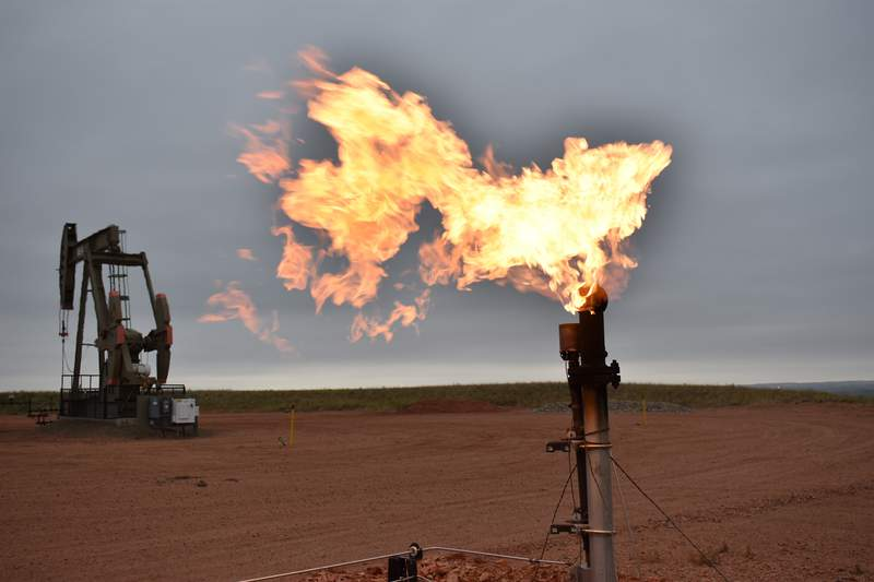 FILE - In this Aug. 26, 2021 file photo, a flare burns natural gas at an oil well Aug. 26, 2021, in Watford City, N.D. Consumers of natural gas are facing the prospect of much higher heating bills this winter. That's after enjoying a prolonged period of low prices.   (AP Photo/Matthew Brown)