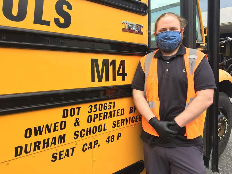 After dropping out of college 10 years ago, Clayton Ward graduated on June 30, 2020 with his associate's degree from MassBay Community College in hopes to become a high school history teacher. In this photo, Ward is seen in front of the school bus he drove while students were still going to school before the Covid-19 pandemic.
