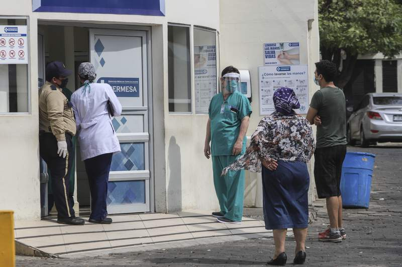 FILE - In this May 11, 2020 file photo, a medical worker wears a mask and face shield at the entrance of the SERMESA hospital in Managua, Nicaragua. While the Pan-American Health Organization urges Nicaragua to take more aggressive measures against the coronavirus pandemic and neighboring countries warily eye its outbreak, President Daniel Ortegas increasingly authoritarian government seems more focused on hiding the virus than treating it. (AP Photo/Alfredo Zuniga, File)