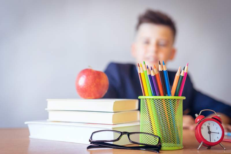 A boy sits at a desk with school supplies.