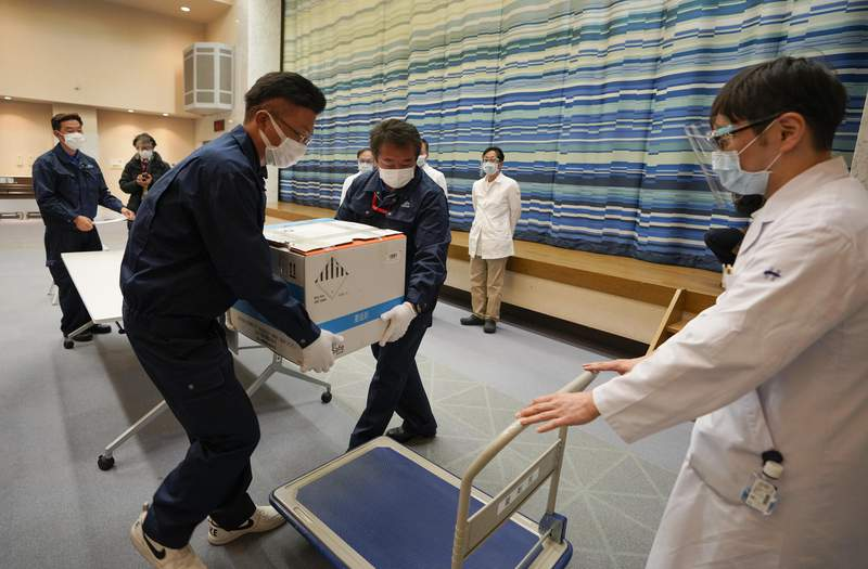 Delivery staff move a box of Pfizer Inc's COVID-19 vaccine on a carriage at the hospital in Tokyo, Japan, Tuesday, Feb. 16, 2021. Japan's COVID-19 vaccinations are scheduled to begin Wednesday after the government granted belated first approval to a shot co-developed by Pfizer Inc. (Kimimasa Mayama/Pool Photo via AP)