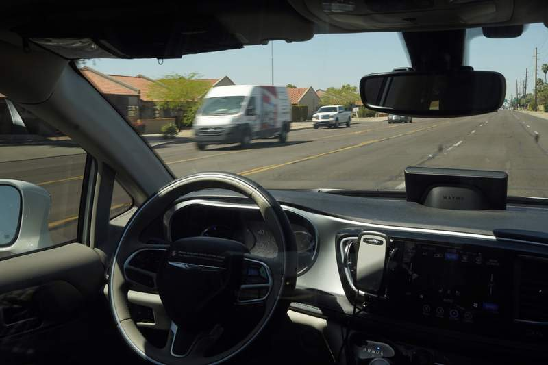 FILE - In this April 7, 2021 file photo, a Waymo minivan moves along a city street as an empty driver's seat and a moving steering wheel drive passengers during an autonomous vehicle ride in Chandler, Ariz.   The U.S. government's highway safety agency has ordered automakers to report any crashes involving fully autonomous vehicles or partially automated driver assist systems. The move Tuesday, June 29,  by the National Highway Traffic Safety Administration indicates the agency is taking a tougher stance on automated vehicle safety than in the past.  (AP Photo/Ross D. Franklin)