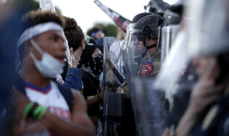 Demonstrators face members of the Austin Police Department as they gather in downtown Austin, Texas, Thursday, June 4, 2020, to protest the death of George Floyd, a black man who was in police custody in Minneapolis. Floyd died after being restrained by Minneapolis police officers on Memorial Day.(AP Photo/Eric Gay)