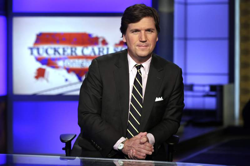 """FILE - In this March 2, 2017 file photo, Tucker Carlson, host of """"Tucker Carlson Tonight,"""" poses for photos in a Fox News Channel studio, in New York. Tucker Carlsons top writer has resigned from Fox News after secretly posting racists and sexist remarks online. CNN reported Friday, July 10, 2020 that writer Blake Neff used a pseudonym to write bigoted comments about Black and Asian people, as well as women, on the online platform AutoAdmit.(AP Photo/Richard Drew, File)"""