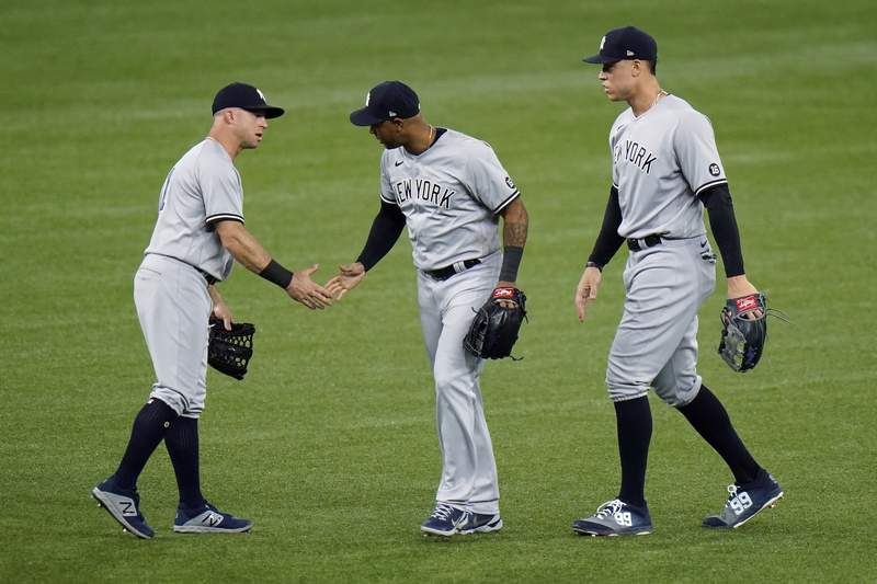 New York Yankees left fielder Brett Gardner, left, center fielder Aaron Hicks, center, and right fielder Aaron Judge celebrate after the team defeated the Tampa Bay Rays during a baseball game Wednesday, May 12, 2021, in St. Petersburg, Fla. (AP Photo/Chris O'Meara)
