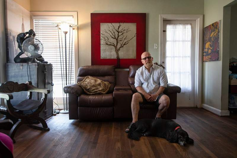 Tomas Garcia sits in his home with his dog, Patches, in Houston on Sept. 8, 2021.