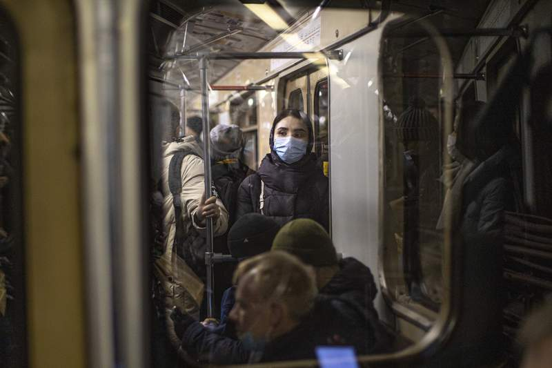 A woman wearing a face mask to help curb the spread of the coronavirus rides a subway car in Moscow, Russia, Monday, Jan. 11, 2021. Russia has continued to face high numbers of new infections even as it has launched a mass vaccination effort. (AP Photo/Alexander Zemlianichenko)
