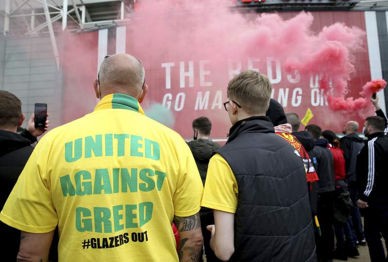 """A fan wears a shirt with a """"United Against Greed"""" message, as fans gather to protest against the Glazer family, the owners of Manchester United, outside Old Trafford stadium, in Manchester, England, before their English Premier League match against Liverpool, Sunday, May 2, 2021. Manchester United supporters have stormed into the stadium and onto the pitch ahead of Sunday's game against Liverpool as fans gathered outside Old Trafford to protest against the Glazer ownership. (Barrington Coombs/PA via AP)"""