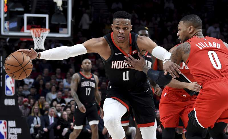 FILE - In this Jan. 29, 2020, file photo, Houston Rockets guard Russell Westbrook, left, dribbles next to Portland Trail Blazers guard Damian Lillard, right, during the first half of an NBA basketball game in Portland, Ore. Westbrook said Monday, July 13, 2020, that he has tested positive for coronavirus, and that he plans to eventually join his team at the restart of the NBA season. Westbrook made the revelation on social media. As recently as Sunday, the Rockets believed that Westbrook and James Harden  neither of whom traveled with the team to Walt Disney World near Orlando last week  would be with the team in the next few days. In Westbrook's case, that now seems most unlikely. (AP Photo/Steve Dykes, File)