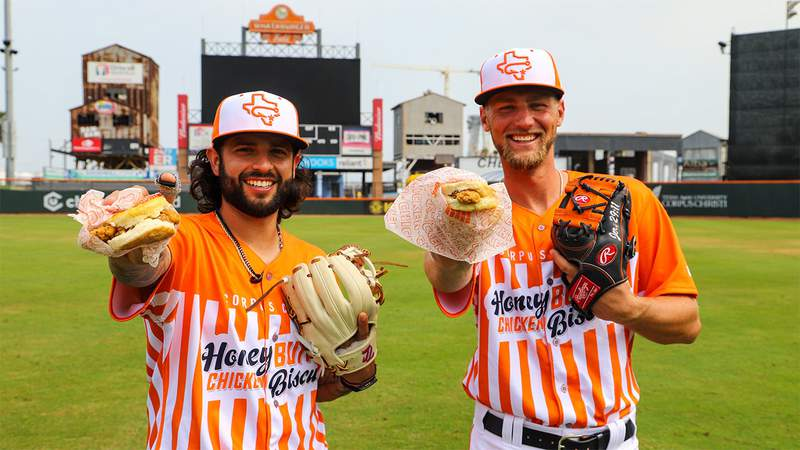 Corpus Christi Hooks players hold biscuits while sporting the team's Whataburger-themed jerseys.