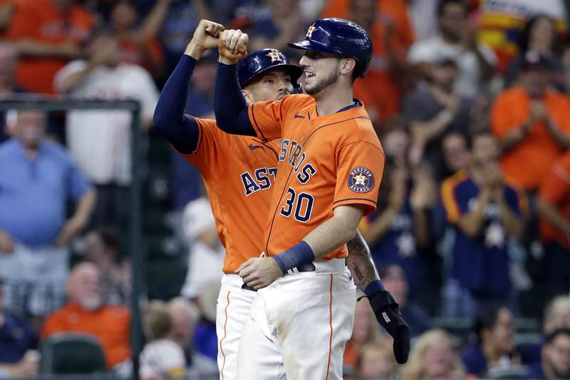 Houston Astros shortstop Carlos Correa, left, and Kyle Tucker (30) celebrate after they scored on Tucker's three-run home run against the Texas Rangers during the third inning of a baseball game Friday, July 23, 2021, in Houston. (AP Photo/Michael Wyke)