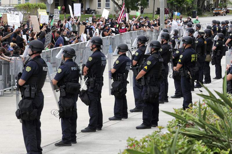 """FILE - In this June 3, 2020 file photo, protesters shout at officers lined up in front of the Orlando Police Department in Orlando, Fla. Hundreds of officers across the country were fired, sometimes repeatedly, for violating policies but got their jobs back after appealing their cases to an arbitrator who successfully overturned their discipline  a all-too-common practice that experts say stands in the way of real accountability. On Monday, June 22, 2020 James Pasco, executive director of the National Fraternal Order of Police,  said """" management should do a better job when hiring officers. (Joe Burbank/Orlando Sentinel via AP)"""