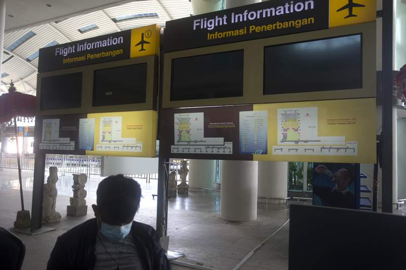 Flight information screens are blank at International Ngurah Rai Airport before its reopening in Bali, Indonesia, Thursday, Oct. 14, 2021. The Indonesian resort island of Bali welcomed international travelers to its shops and white-sand beaches for the first time in more than a year Thursday - if they're vaccinated, test negative, hail from certain countries, quarantine and heed restrictions in public. (AP Photo/Firdia Lisnawati)