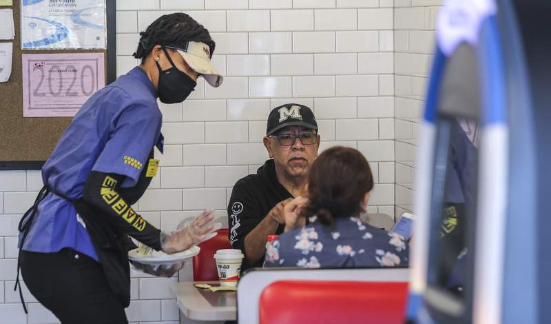 Waffle House's Miss D, left, serves Daniel Bahena and his guest, right, on Monday, April 27, 2020 at The Waffle House in Brookhaven, Ga. Restaurants around metro Atlanta began to reopen dining rooms Monday, April 27, 2020 as restrictions related to the coronavirus pandemic are lifted. Restaurants will be allowed to operate with in-person dining as long as they follow a set of 39 guidelines laid out by the state government, which include a requirement that all employees wear masks, a maximum of 10 customers per 500 square feet of floor space and a maximum of six diners per table.(John Spink/Atlanta Journal-Constitution via AP)