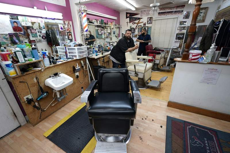 Carlos Vasquez, left, and his nephew R.J. Vasquez, wait for customers at their family's barber shop Friday, March 20, 2020, in Houston. The barbers at family-owned barber shop estimate they have lost nearly half of their business due to the coronavirus. (AP Photo/David J. Phillip)