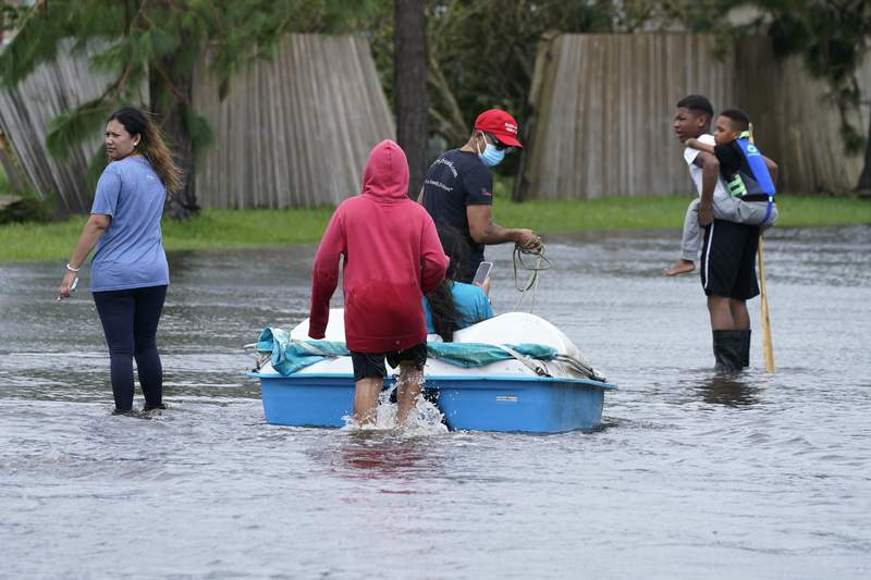Residents walk a boat back into a flooded neighborhood to retrieve belongings after Hurricane Ida moved through Monday, Aug. 30, 2021, in LaPlace, La. (AP Photo/Steve Helber)