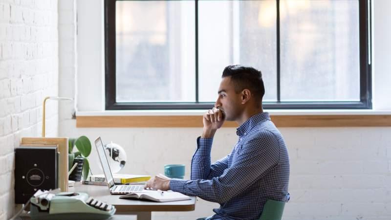 A man sits at a desk, going through his computer.