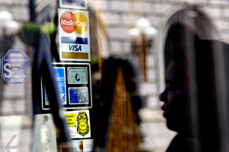 FILE - In this July 18, 2012, file photo, credit logos are displayed on a downtown storefront as a pedestrian passes in Atlanta.  U.S. consumer borrowing rose by a solid 3.6% in July, the second monthly gain after the coronavirus pandemic had sent consumer borrowing down sharply in the previous three months, the Federal Reserve reported Tuesday, Sept. 8, 2020. (AP Photo/Ashley Hopkinson, File)