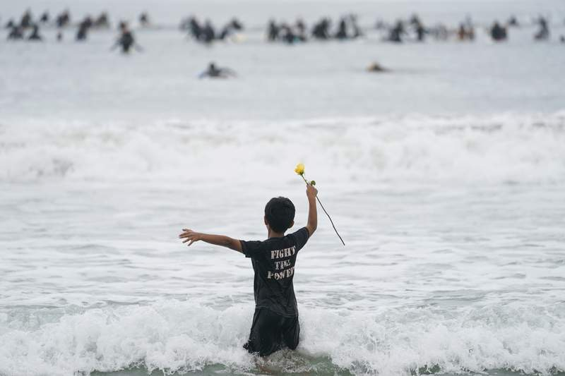 """Nathan Rangel, 11, jumps in the water carrying a rose as surfers participate in a paddle out ceremony at """"The Ink Well,"""" a beach historically known as a surfing refuge for African Americans, to honor the life of George Floyd on Friday, June 5, 2020, in Santa Monica, Calif. Floyd died after he was restrained in police custody on Memorial Day in Minneapolis. (AP Photo/Ashley Landis)"""